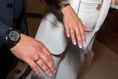 Brud- och brudgumvisningvigselringar på deras fingrar kvinnlign hands att gifta sig för manligcirklar fotografering för bildbyråer