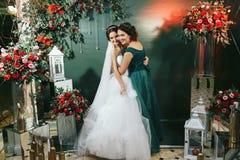 Brud- och brudtärnakram bland de röda buketterna Royaltyfria Bilder