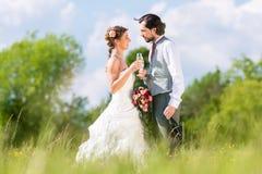 Brud- par firar bröllopdag med champagne arkivbild