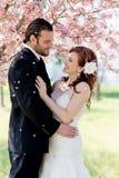 Brud- par som duschas av Cherry Blossom Petals Royaltyfri Foto