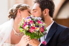 Brud- par som ger kyssen i kyrka på bröllop Fotografering för Bildbyråer
