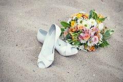 Brud- skor och bröllopbukett Arkivbild