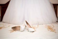 Brud- skor och klänning Arkivfoton