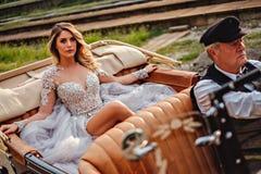 Brud som är drivande vid den gamla chauffören i en klassikercabriolet Royaltyfria Foton