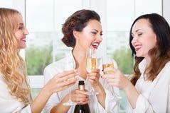 Brud som är, och bridemaids som rymmer som är glass med champagne Arkivfoton
