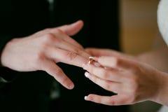 Brud som bär vigselringen på brudgum Hon satte cirkeln på honom Arkivbild