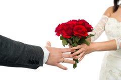 Brud som erbjuder den rosa buketten till brudgummen Royaltyfri Bild