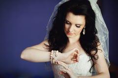 Brud som försöker på smycken på bröllopdagen Royaltyfria Foton