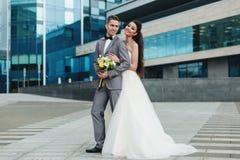 Brud som framme kramar brudgummen av byggnaden Royaltyfri Bild