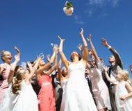 Brud som kastar buketten för gäster till låset Royaltyfri Foto