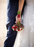 Brud som kramar brudgum- och innehavbröllopbuketten Arkivbild