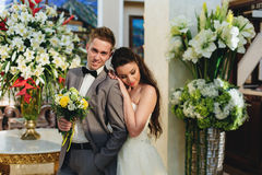 Brud som kramar brudgummen på bakgrunden av blommor Arkivbilder