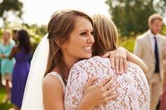 Brud som kramar modern på bröllopdag royaltyfri foto