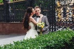 Brud som kysser hennes le brudgum Arkivfoton