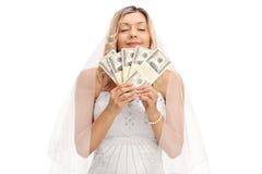 Brud som luktar buntar av pengar Royaltyfria Foton