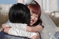 brud som omfamnar lyckligt le för brudgum Royaltyfri Foto