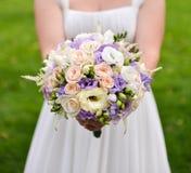 Brud som rymmer den härliga bröllopbuketten med färgrika blommor Arkivbilder
