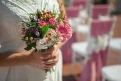 Brud som rymmer den lilla bröllopbuketten i händer Arkivfoto