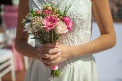 Brud som rymmer den lilla bröllopbuketten i händer Fotografering för Bildbyråer
