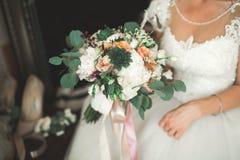 Brud som rymmer den stora och härliga bröllopbuketten med blommor Arkivbild