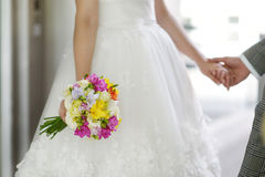 Brud som rymmer en bröllopbukett Arkivfoto