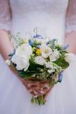 Brud som rymmer en bröllopbukett i en parkera, närbild, selektivt f Royaltyfri Bild