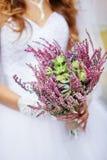 Brud som rymmer en härlig bröllopbukett av lösa blommor fotografering för bildbyråer