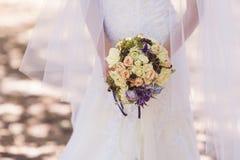 Brud som rymmer en härlig brud- bukett på gå Royaltyfria Bilder