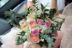 Brud som rymmer en härlig brud- bukett Bröllopbukett av persikarosor av David Austin, aqua för singel-huvud rosa färgros, eukalyp Royaltyfri Bild