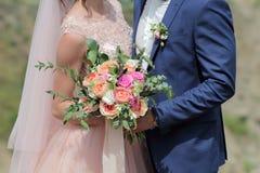 Brud som rymmer en härlig brud- bukett Bröllopbukett av persikarosor av David Austin, aqua för singel-huvud rosa färgros, eukalyp arkivbild
