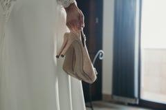 Brud som rymmer ett par av brud- skor i handen som är främst av ett fönster Arkivfoton