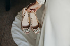 Brud som rymmer ett par av brud- skor i handen Fotografering för Bildbyråer