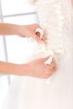 Brud som sätter den vita bröllopsklänningen Royaltyfria Foton
