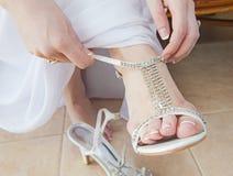 Brud som sätter på bröllopsandaler Arkivbilder