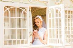 Brud som ser till och med fönstret Royaltyfria Bilder