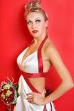 Brud som slitage i klänning med röda band Arkivbild