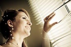 brud som ut ser det nätt fönstret Arkivfoto