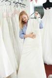 Brud som väljer klänningen i brud- boutique Royaltyfria Foton