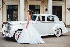 Brudanseende vid den klassiskt bilen och le royaltyfria foton