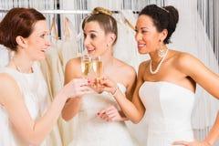 Brudar som dricker champagne i bröllop, shoppar Fotografering för Bildbyråer