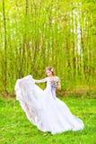 Brudbröllopsklänningen framkallar i luften mot grönt fält Royaltyfri Foto