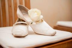 Brudbröllopskor på stol med rosen royaltyfria foton