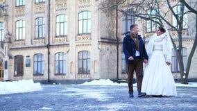 brudbrudgum som gifta sig utomhus vinter nygift personpar i bröllopsklänningar går till och med snö-täckt parkerar, mot bakgrunde arkivfilmer