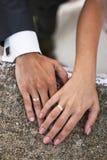brudbrudgummen hands bröllop för cirklar s Arkivfoto