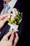 Bruden bär en boutonnierebrudgum Arkivbilder