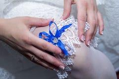 Bruden bär en vit strumpeband för snöra åt på hennes ben Arkivfoto