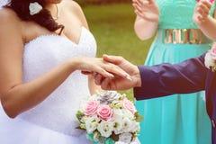 Bruden bar en guld- vigselring på fingret av bruden, räcker endast tätt br?llop royaltyfri fotografi