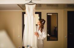 Bruden betraktar en bröllopsklänning Arkivbild