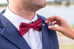 Bruden hjälper brudgummen att justera handtag den röda flugan Royaltyfria Foton