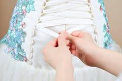 Bruden hjälps att snöra åt upp korsetten royaltyfri foto